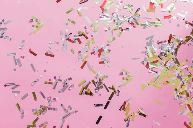 Close-up di coriandoli colorati su sfondo rosa