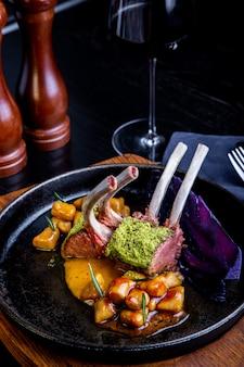 Close up di costolette di agnello con verdure con salsa di caramello, pepe e spezie in un ristorante.