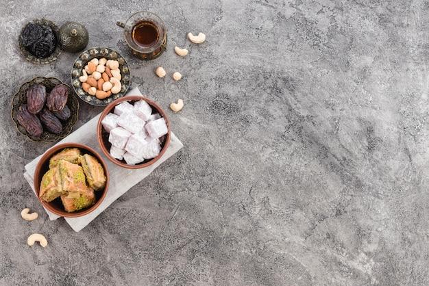 Close-up di delizie tradizionali turche lukum e baklava con frutta secca su sfondo grigio concreto