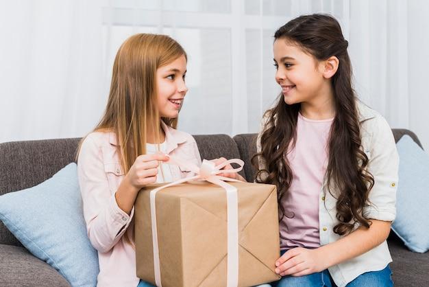 Close-up di due amici femminili seduti sul divano a guardare l'altro mentre si apre il contenitore di regalo