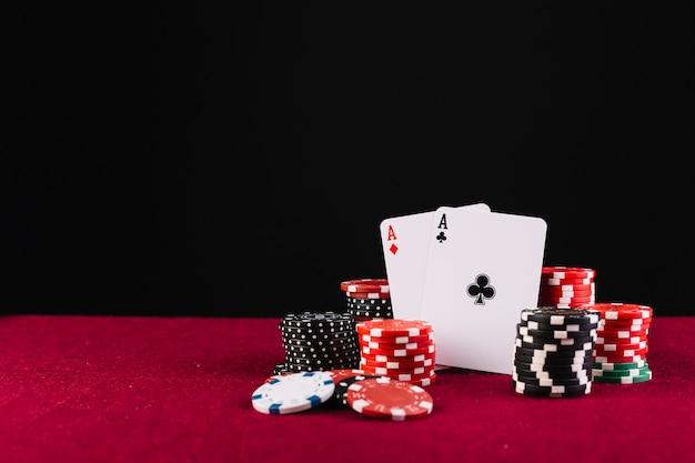 Close-up di due assi di carte da gioco e fiches da poker su sfondo rosso