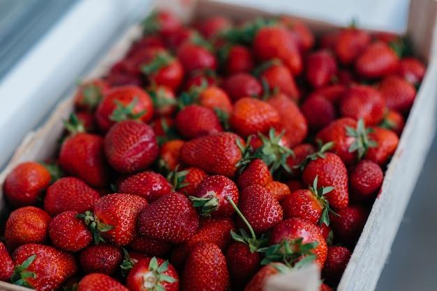 Close-up di fragole fresche mature in un contenitore in vendita. dieta sana.
