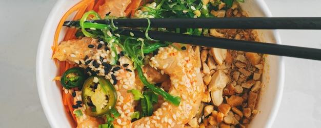 Close-up di gamberi piccanti poke bowl con riso, alghe e semi di sesamo, avocado in una scatola di pranzo con le bacchette su bianco. pranzo sano a base di pesce. dieta alimentare. vista dall'alto con spazio di copia.