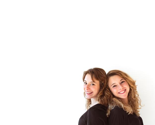 Close-up di giovani sorelle in piedi schiena contro schiena in piedi su sfondo bianco