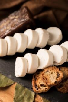 Close-up di gustosi pezzi di formaggio di capra e pane tostato sul vassoio nero