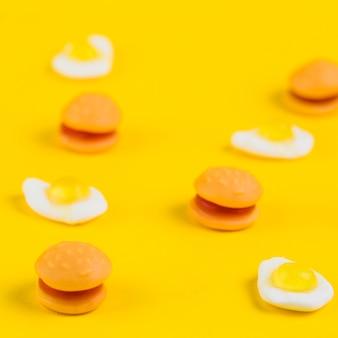 Close-up di hamburger caramelle e gummies uovo fritto su sfondo giallo