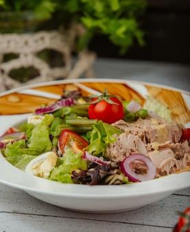 Close up di insalata di tonno con uova, cipolla, lattuga, pomodoro e piselli