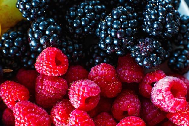 Close-up di lampone e bacche di gelso nero split frame. vitamine estive, bacche dolci.