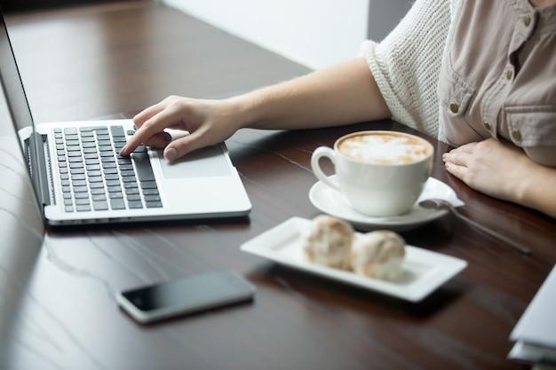 Close-up di mani femminili lavorando al computer portatile in caffè