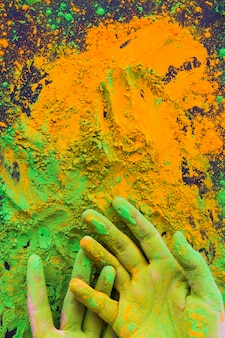 Close-up di mano dipinta con polvere di colore holi