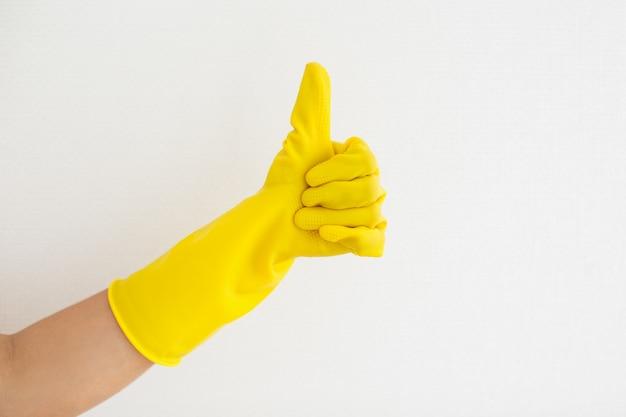 Close-up di mano in guanto di gomma mostrando thumb-up