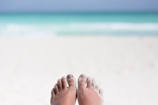 Close-up di piedi coperti di sabbia in spiaggia