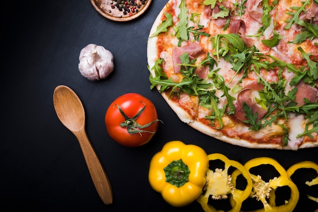 Close-up di pizza con foglie di rucola; fette di peperone giallo; bulbo di pomodoro e aglio su sfondo nero