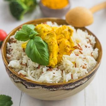 Close-up di riso bollito fresco; foglie di basilico e pollo fritto in una ciotola con un cucchiaio di legno