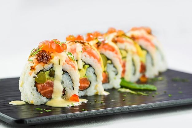 Close-up di rotoli tradizionali giapponesi e sushi su un piatto di pietra nera