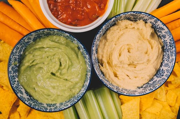 Close-up di salsa guacamole e salsa in una ciotola su carota; gambo di sedano e tortilla