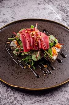 Close up di sashimi sushi con bistecca di tonno crudo, avocado, cetriolo e formaggio philadelphia e bacchette su elegante piastra nera