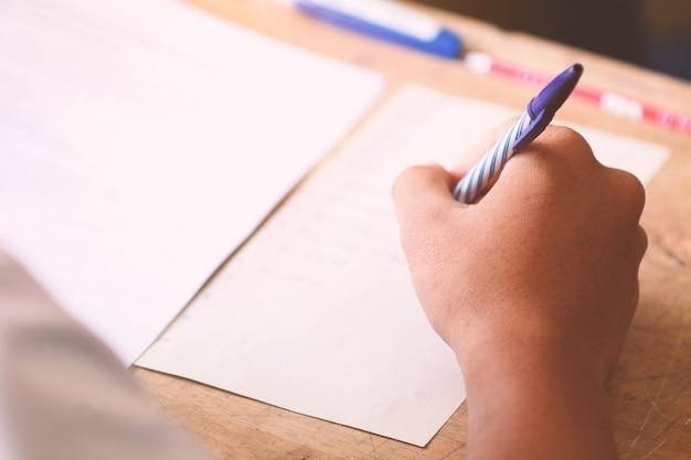 Close-up di scrivere le mani di studenti uniformi per testare a scuola