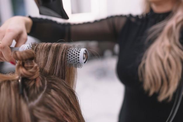 Close-up di stilista che fissa i capelli