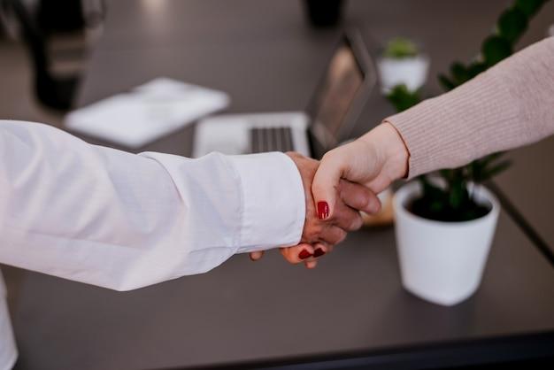 Close-up di stringere la mano dopo una riunione di lavoro in ufficio