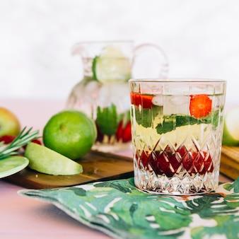 Close-up di succo sano con ingredienti vicino frutti sul tagliere