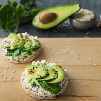 Close-up di torta di riso con fette di avocado; sul tagliere di legno