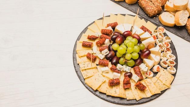 Close-up di un piatto di formaggi con uva e salsicce affumicate sul bordo di ardesia