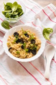 Close-up di una ciotola di avena sano guarnito con foglie di basilico e olive per la colazione