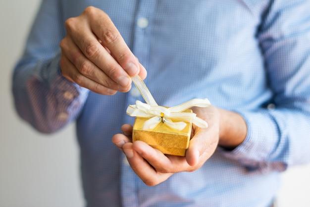 Close-up di uomo sciogliere arco sulla piccola scatola gialla