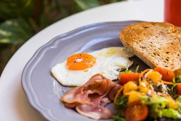 Close-up di uova fresche fritte; bacon; pane tostato e insalata servita sul piatto grigio sopra il tavolo bianco