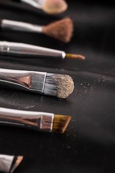 Close-up di vari pennelli trucco su sfondo nero