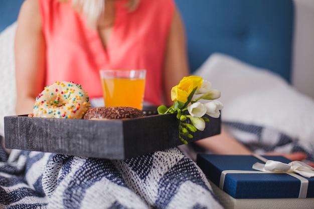 Close-up di vassoio colazione accanto a un regalo
