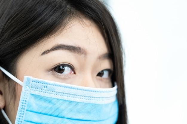 Close up donna con mal di testa indossando maschera per proteggere covid-19