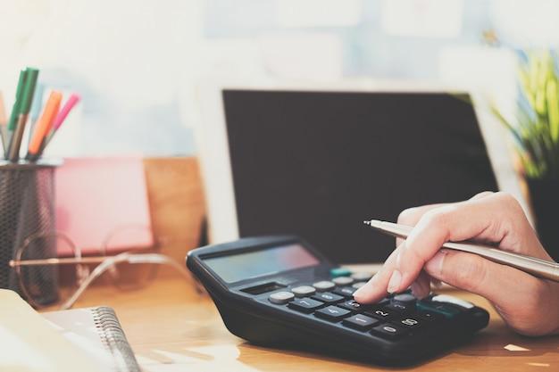 Close up donna d'affari utilizzando calcolatrice e laptop per fare matematica matematica sulla scrivania in legno in ufficio e business di lavoro sfondo, tasse, contabilità, statistiche e concetto di ricerca analitica