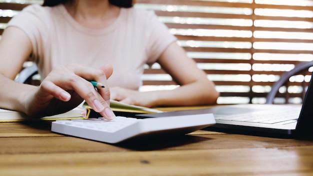 Close up donna d'affari utilizzando calcolatrice e laptop per fare matematica matematica sulla scrivania in legno in ufficio e lavoro aziendale, fiscale, contabilità, statistiche e concetto di ricerca analitica