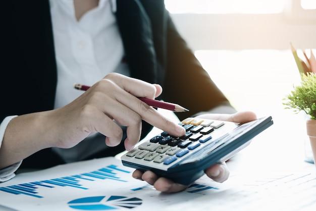 Close up donna d'affari utilizzando la calcolatrice per fare matematica matematica sulla scrivania in legno in ufficio e lavoro aziendale, fiscale, contabilità, statistiche e concetto di ricerca analitica