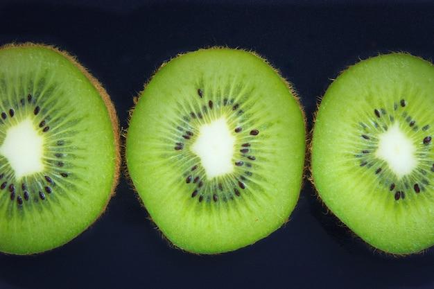 Close up fette organiche kiwi su sfondo nero