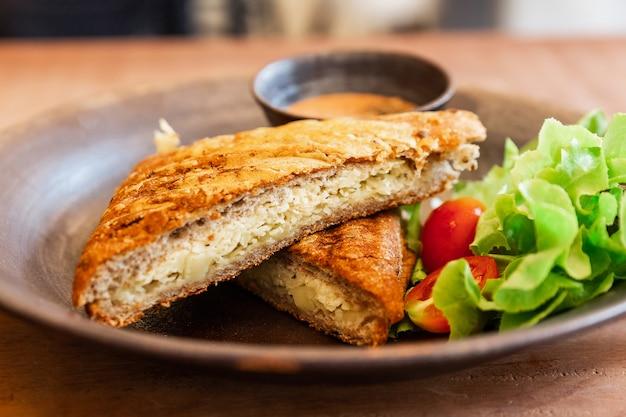 Close-up griglia formaggio panino al grano servito con salsa mille isole e insalata tra quercia verde e pomodoro su un piatto di ceramica. panino al formaggio grigliato a casa per la colazione.