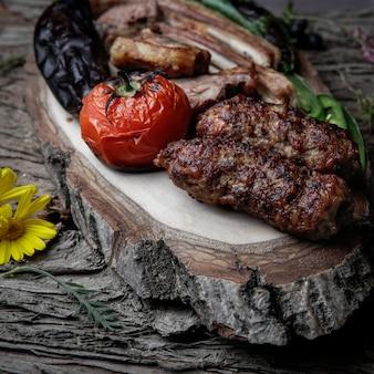 Close-up kebab costolette alla griglia kebab con pomodoro al forno, pepe e melanzane su un piatto di legno su una corteccia di legno scuro