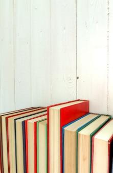 Close up libro rosso romanzo estende lo sfondo è un muro di legno bianco.