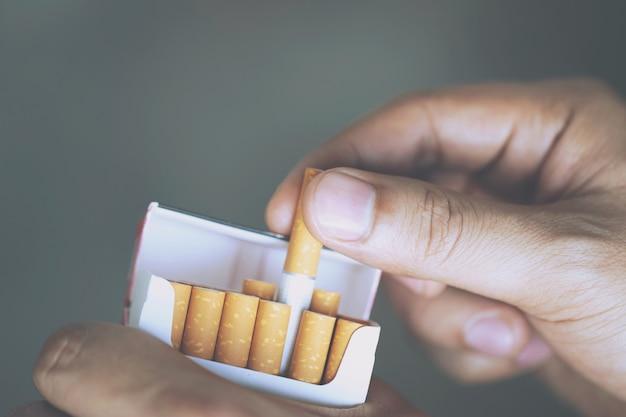 Close up man mano che tiene sbucciare fuori pacchetto di sigarette preparare fumare una sigaretta.
