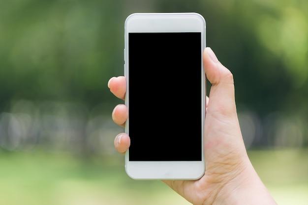Close-up mano mostrando sul telefono mobile nero vuoto schermo concetto di lifestyle all'aperto sullo sfondo sfocato della natura - può essere utilizzato immagine imbrattata. immagini di stile d'effetto vintage.
