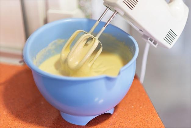 Close up mescolando la pasta biscotto con un mixer elettrico. profondità di campo