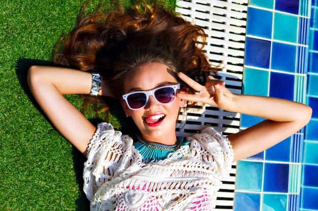 Close up moda estate ritratto di splendida bella donna, posa vicino alla piscina, rilassarsi e prendere il sole. accessori e gioielli alla moda, stile di vacanza di lusso, colori luminosi tonificati.