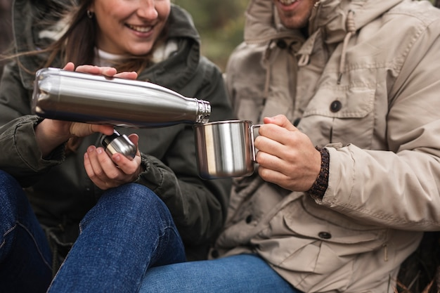 Close-up persone con thermos e tazza