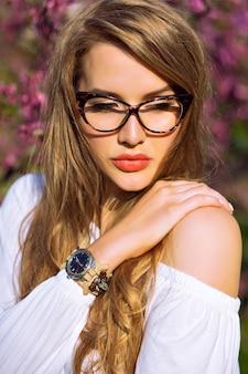 Close up primavera estate ritratto di splendida giovane donna con capelli lunghi naturali incredibili e bellezza viso, indossando occhiali trasparenti, colori solari.