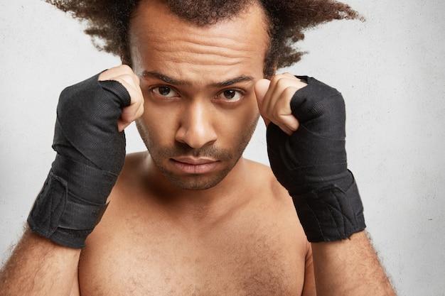 Close up ritratto del pugile maschio di successo mostra forti braccia e pugni chiusi avvolti da bende protettive