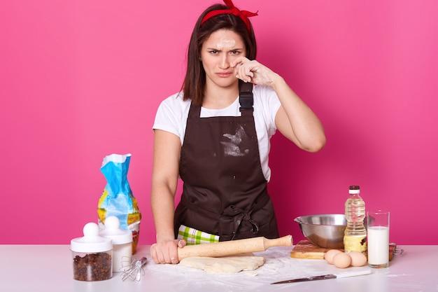 Close up ritratto di adorabile casalinga o fornaio sembra stanco e triste, passa molte ore in cucina, ha la faccia sporca con farina, tiene il mattarello e stende la pasta isolata sulla parete rosa.