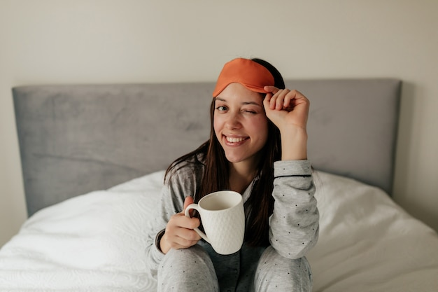 Close up ritratto di affascinante donna sorridente nel letto con la tazza di caffè al mattino ammiccante e tenendo la maschera per dormire.