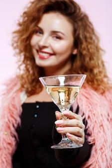 Close up ritratto di allegro sorridente bella ragazza bruna riccia in pelliccia rosa azienda cocktail su muro bianco focus sul vetro.
